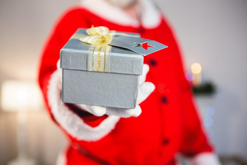 Weihnachtsmann, der ein Geschenk gibt stockbilder