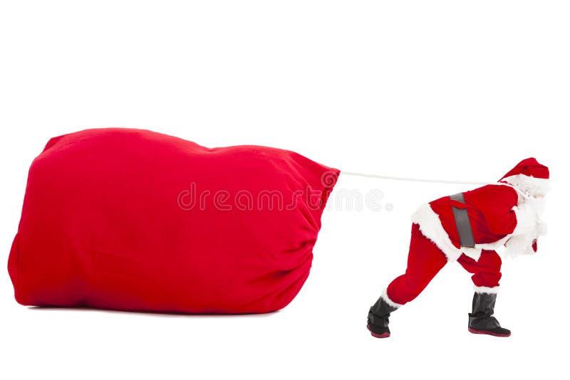 Weihnachtsmann, der einen schweren Geschenksack trägt stockfotografie