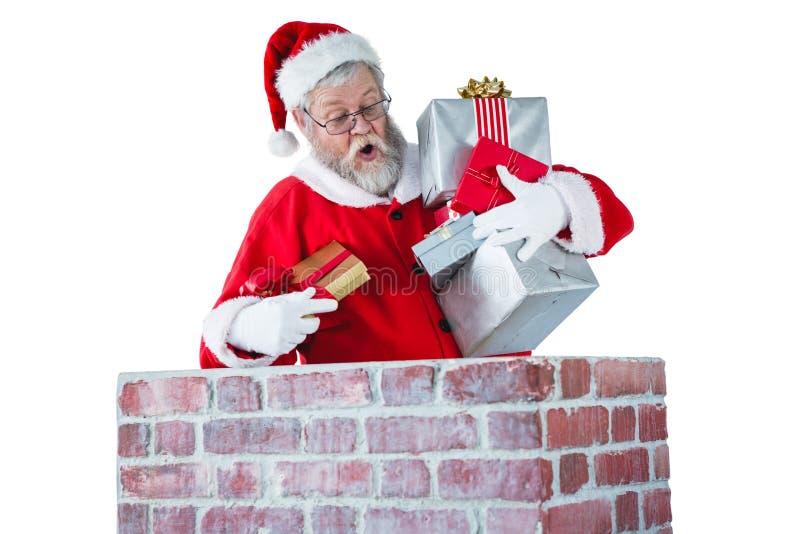 Weihnachtsmann, der Geschenkbox in einen Kamin setzt stockfotografie