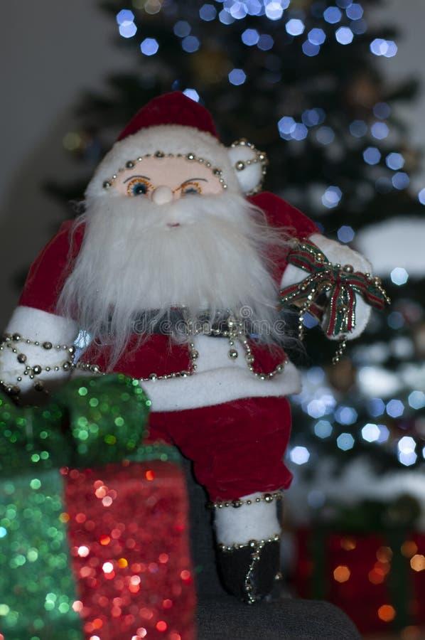 Weihnachtsmann, der nahe bei Weihnachtsbaum und Ihrer Geschenkbox sitzt lizenzfreie stockfotos