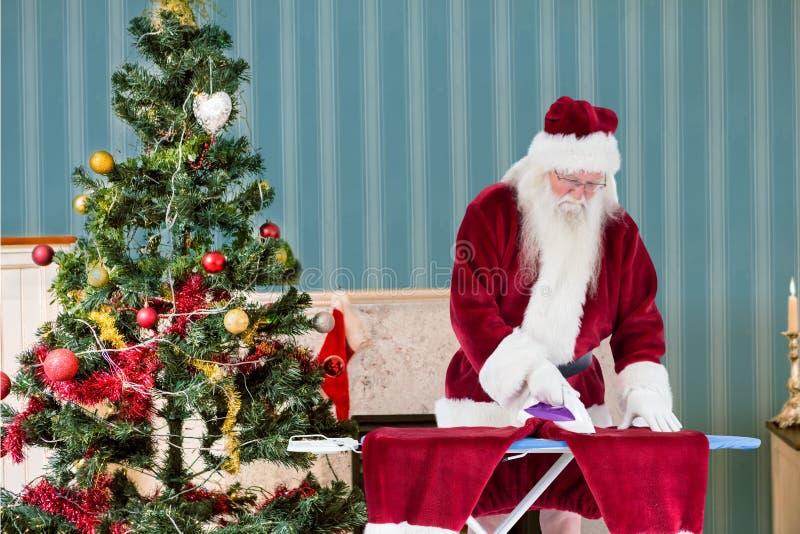 Weihnachtsmann, der seine Kleidung bügelt stockbilder