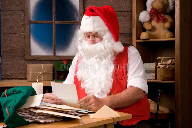 Weihnachtsmann in der Werkstatt mit Zeichen stockbilder