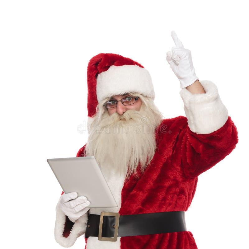 Weihnachtsmann hält Tablette und Punktfinger hoch stockbilder