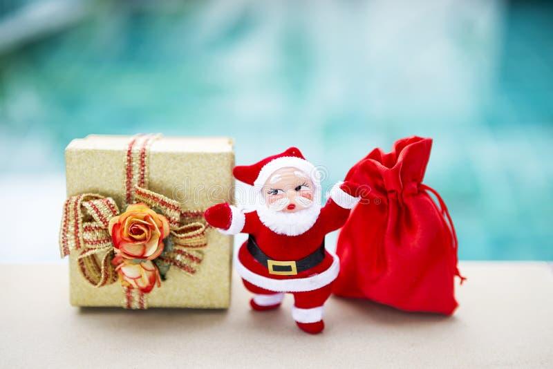Weihnachtsmann mit Goldgeschenkbox und roter Tasche über unscharfem blauem Hintergrund stockbild