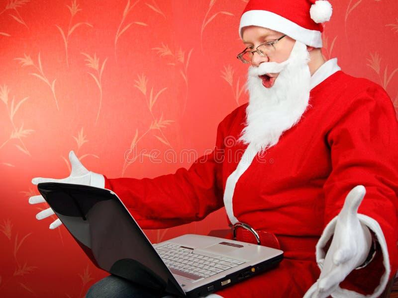 Weihnachtsmann mit Laptop stockfoto