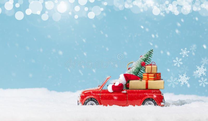 Weihnachtsmann in Rotem Auto mit Weihnachtsbaum und schneebedeckten Geschenken Weihnachtsgebirge Urlaubskarte lizenzfreie stockfotografie
