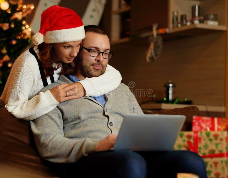 Weihnachtsmann und roter Ball Frau in Sankt-` s Hut, der einen Mann verwendet einen Laptop umarmt stockfotos