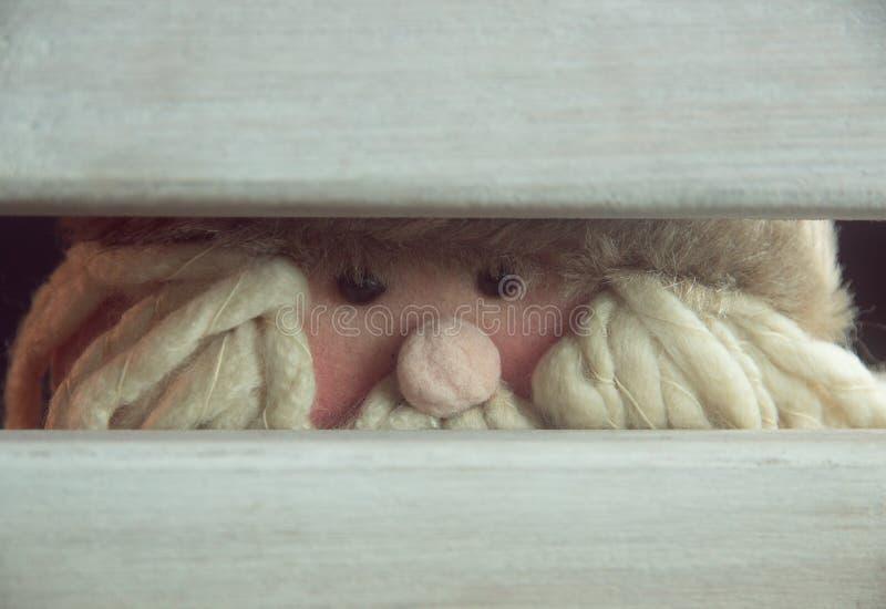 Weihnachtsmann versteckt hinter einem Stuhl lizenzfreie stockbilder