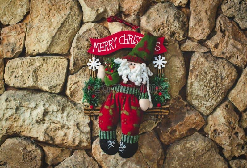 Weihnachtsmann-Weihnachtsdekoration gemacht mit der gestrickten Wolle, die auf einem Steinwandhintergrund hängt lizenzfreie stockbilder