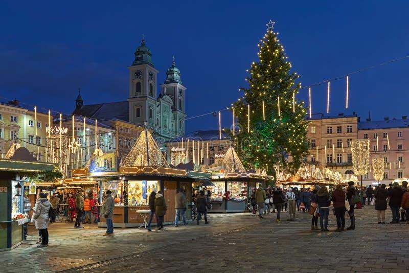 Weihnachtsmarkt am Hauptplatz von Linz in der Dämmerung, Österreich stockfotografie