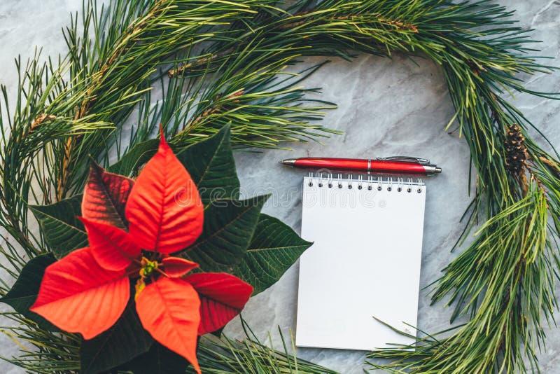 Weihnachtsnahaufnahmemodell mit Poinsettia, Kiefernkranz, Notizbuch, mit Kopienplatz lizenzfreie stockfotos