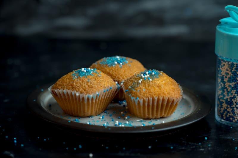 Weihnachtsnahrung - die Zitronenmuffins, die mit Blauem und weißem besprüht werden, besprüht lizenzfreie stockbilder