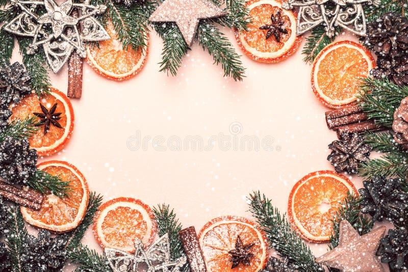 Weihnachtsnatürlicher Rahmen von trockenen Orangenscheiben, -Tannenzapfen und -niederlassungen Weinlesetonen und -schnee stockfotografie