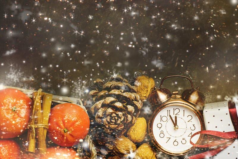 Weihnachtsneues Jahr-Gruß-Karten-Tangerinen in den Korb-Wecker-Kiefern-Kegel-Geschenkbox-Schnee-Flocken stockfotografie