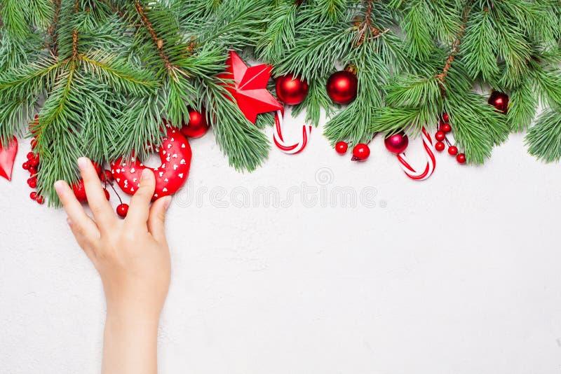 Weihnachtsniederlassung und -glocken Wenig Babyhand mit Donut stockbilder