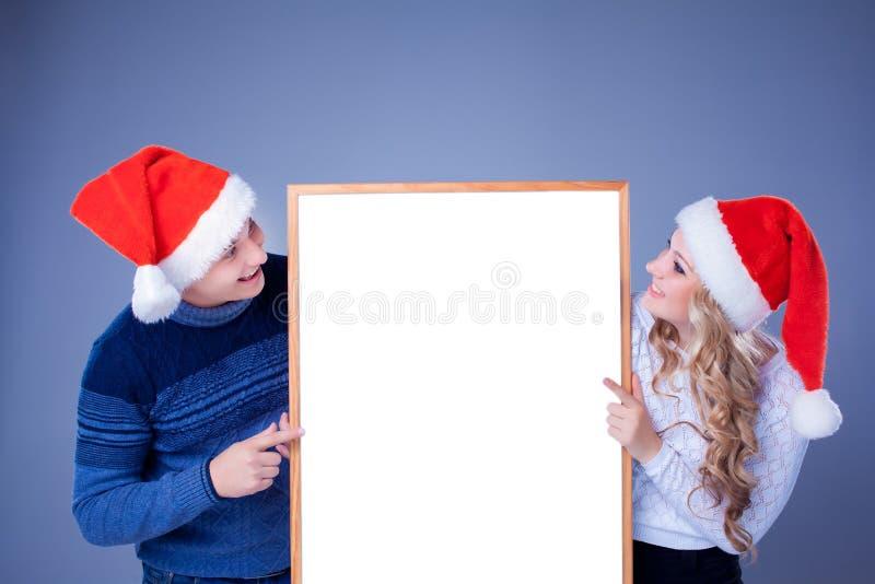 Weihnachtspaare, die weißes Brett mit leerem halten stockbilder