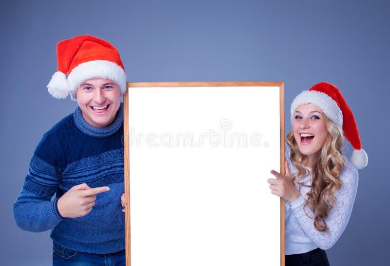 Weihnachtspaare, die weißes Brett mit leerem halten stockfoto