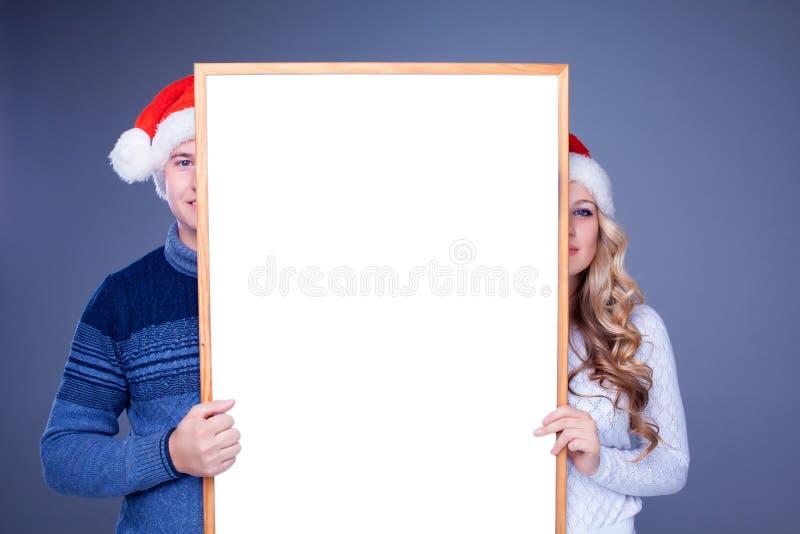 Weihnachtspaare, die weißes Brett mit leerem halten lizenzfreies stockbild