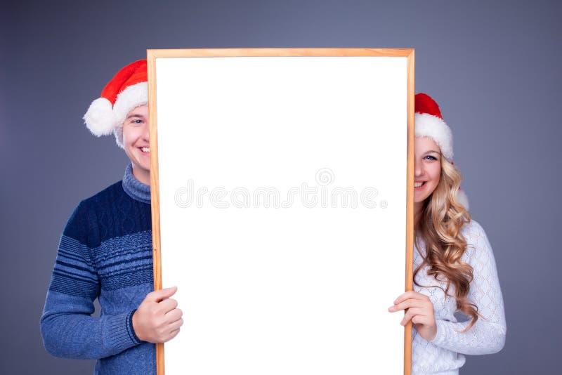 Weihnachtspaare, die weißes Brett mit leerem halten lizenzfreie stockfotos