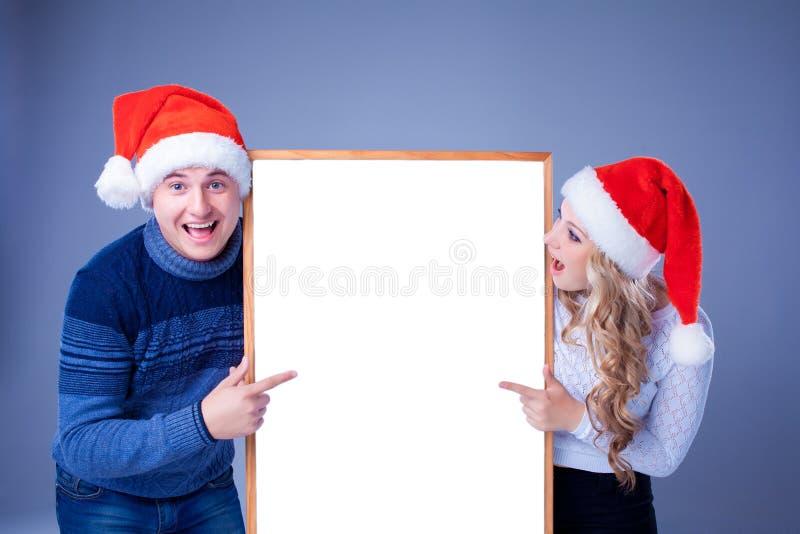 Weihnachtspaare, die weißes Brett mit leerem halten lizenzfreies stockfoto