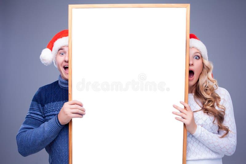 Weihnachtspaare, die weißes Brett mit leerem halten stockbild