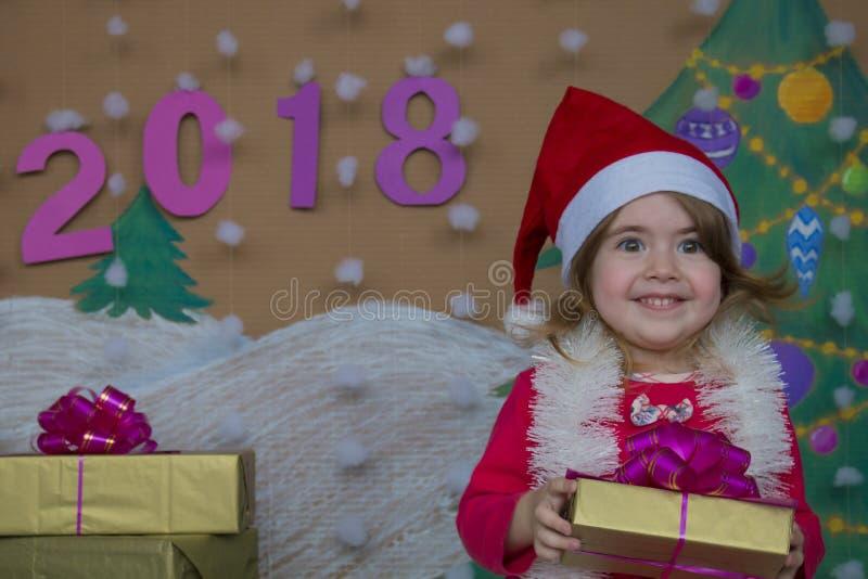 Weihnachtspakete - regalo di Natale 2018 buoni anni Piccola ragazza sveglia che tiene un regalo fotografia stock