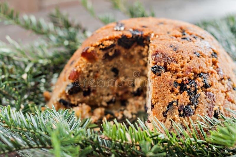 Weihnachtspflaumenpudding im Abschnitt auf Tannenzweigen lizenzfreie stockfotos