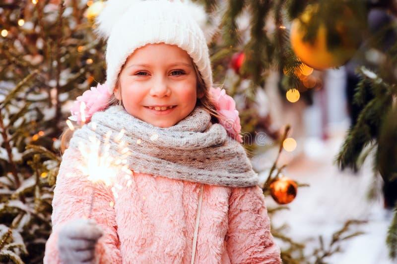 Weihnachtsporträt des glücklichen Kindermädchens, das brennende Wunderkerze halten oder des Feuerwerks im Freien lizenzfreie stockfotografie