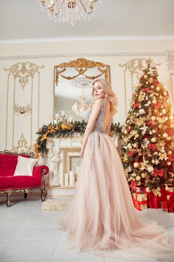 Weihnachtsporträt eines Mädchens in einem funkelnden festlichen Kleid auf dem Hintergrund des Weihnachtsdekors im eleganten Innen lizenzfreie stockbilder