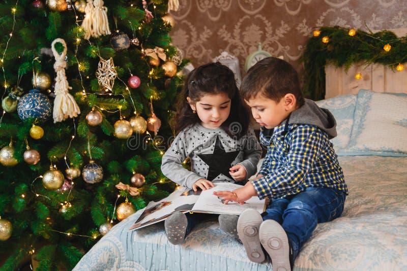 Weihnachtsporträt von den lächelnden Kleinkindern, die auf Bett mit Geschenken unter dem Weihnachtsbaum sitzen Winterurlaub-Weihn stockfotos