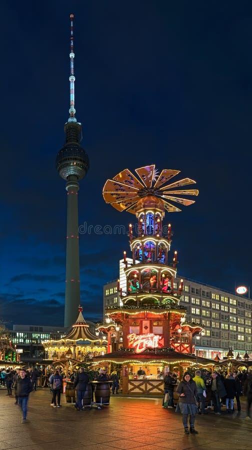 Weihnachtspyramide am Weihnachtsmarkt auf Alexanderplatz und Berlin Fernsehturm, Deutschland lizenzfreie stockfotos