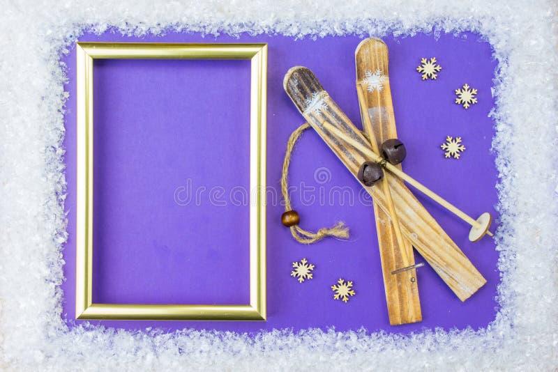 Weihnachtsrahmen besteht aus weißen Verschönerungen: Schneeflocken, Ren, Ski und Geschenkboxen auf blauem Hintergrund E stockfotografie