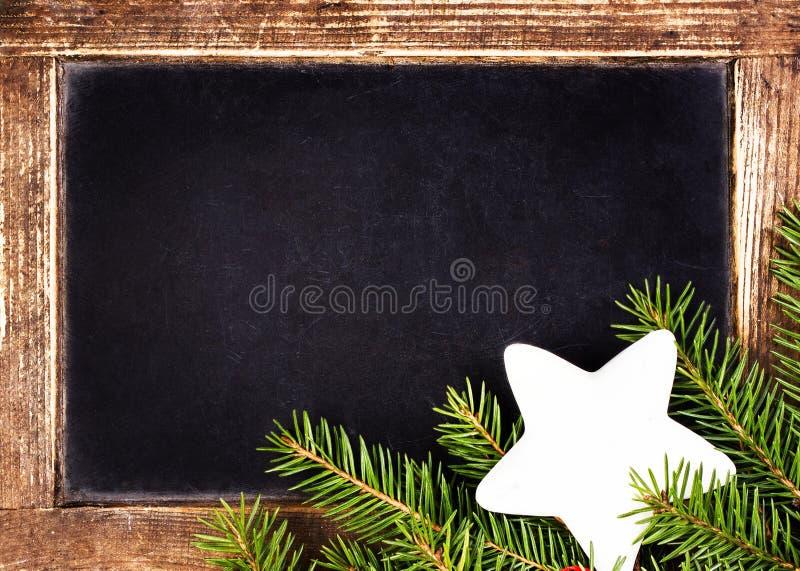 Weihnachtsrahmen mit Holly Decoration auf Weinlese-Tafel.  R lizenzfreie stockfotografie