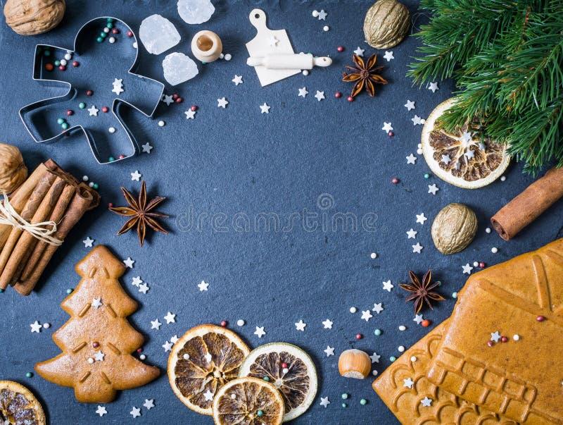 Weihnachtsrahmen mit Plätzchen, Zimt, trockene Orange auf Schwarzem stockfotografie