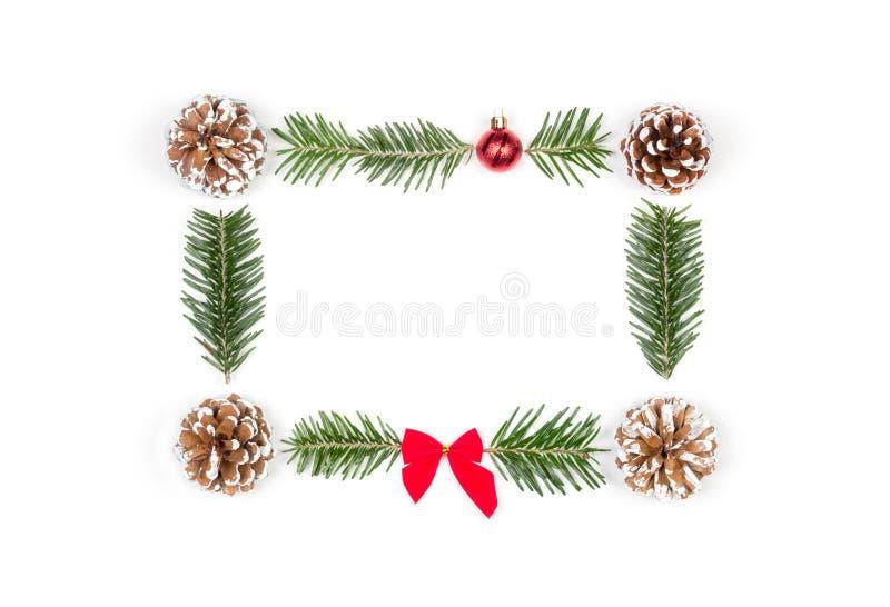 Weihnachtsrahmen von Kiefernkegeln und -Tannenzweigen auf einem weißen Hintergrund stockbilder