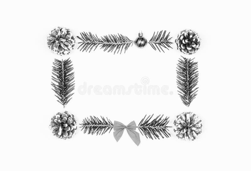 Weihnachtsrahmen von Kiefernkegeln und -Tannenzweigen auf einem weißen Hintergrund Flache Lage, Draufsicht, Kopienraum stockbild
