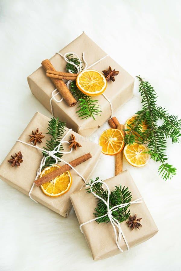 Weihnachtsretro- eingewickelte Geschenke mit Gewürzen, getrocknete orange Scheibe und lizenzfreies stockfoto