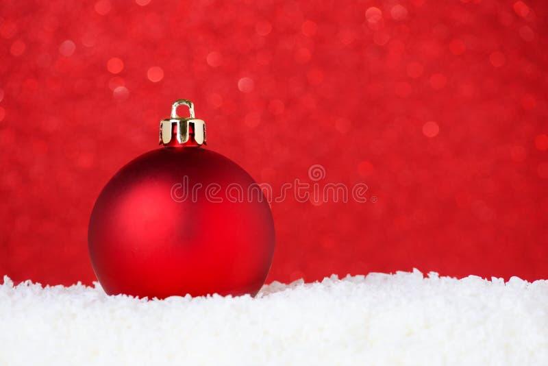 Weihnachtsroter Flitter im Schnee auf rotem Hintergrund mit bokeh, selektivem Fokus und Kopienraum stockbild