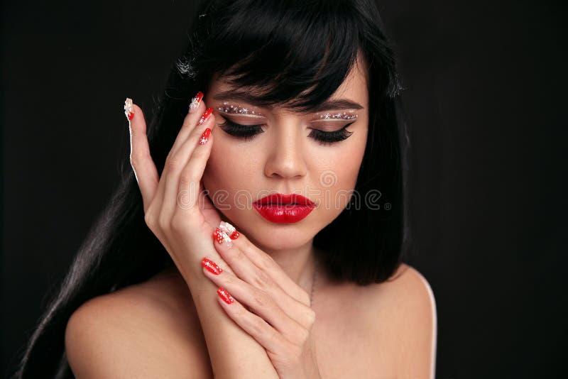 Weihnachtsrotes Lippenmake-up und manikürte Nägel Schönes brunett stockfotografie