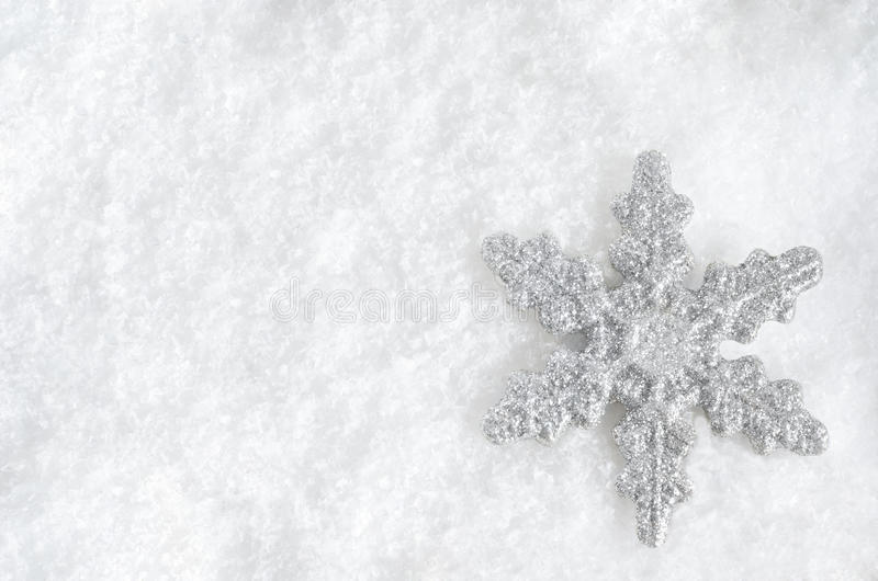 Weihnachtsschneeflocke auf Schnee stockfoto
