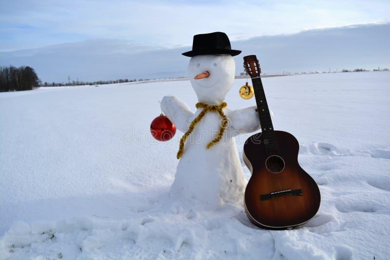 Weihnachtsschneemann mit Flitter, Hut und alter Gitarre stockbild