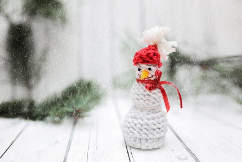 Weihnachtsschneemanndekoration mit Schnee auf weißem hölzernem Hintergrund Postkartenentwurf des Feiertags-neuen Jahres stockbild