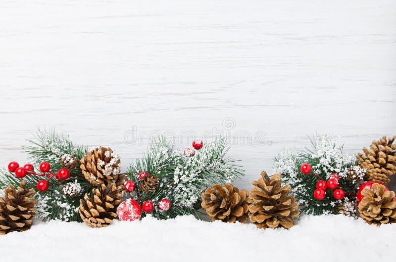 Weihnachtsschneeszene Weihnachtsbaumaste mit Kegeln und Verzierungen auf hölzernem hellem Hintergrund, stockfoto