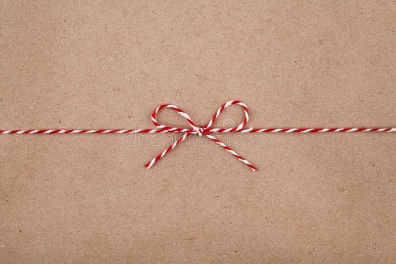 Weihnachtsschnur oder -schnur gebunden in einem Bogen auf Kraftpapierhintergrund lizenzfreie stockfotografie