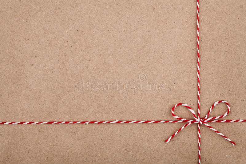 Weihnachtsschnur oder -schnur gebunden in einem Bogen auf Kraftpapierhintergrund stockfotos