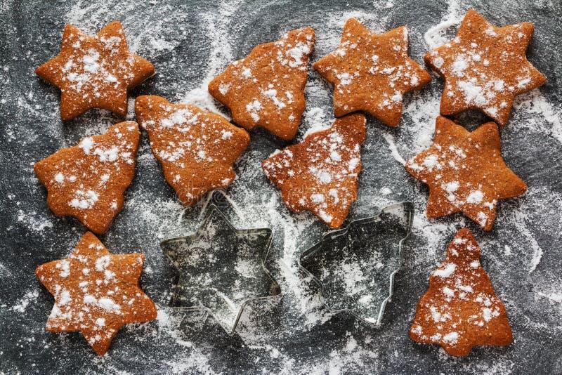 Weihnachtsschwarzer Hintergrund mit Puderzucker und braunen Schokoladen- und Ingwerplätzchen in Form des Tannenbaums und des Ster stockbilder