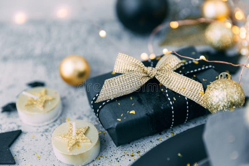 Weihnachtsschwarzes Geschenk mit Golddekorationen stockfoto