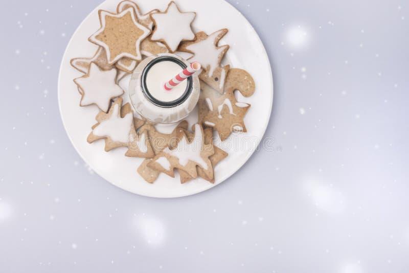 Weihnachtsselbst gemachte Lebkuchen-Plätzchen auf hellblauer Hintergrund-flacher gelegter Feiertags-Konzept-Glasflasche mit Milch stockfotografie