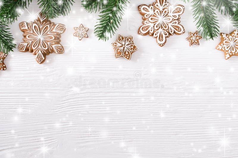 Weihnachtsselbst gemachte Lebkuchenplätzchen und -Tannenzweige auf weißem hölzernem Hintergrund stockbild