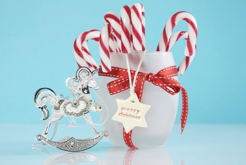 Weihnachtssilberne Weinleseschaukelpferd-Baumverzierung und Glas Zuckerstangen lizenzfreies stockfoto